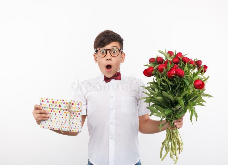 有礼物和花的震惊男孩 库存照片