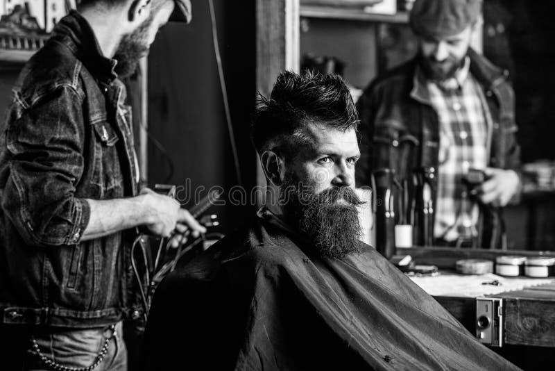 有称呼残酷有胡子的客户的头发的飞剪机的理发师 得到理发的行家客户 行家生活方式概念 库存图片