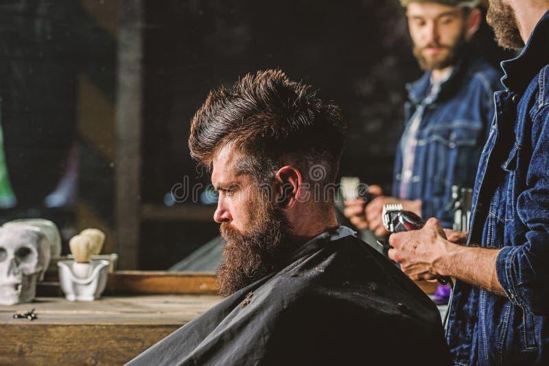 有称呼残酷有胡子的客户的头发的飞剪机的理发师 行家生活方式概念 有头发剪刀的理发师工作  库存图片