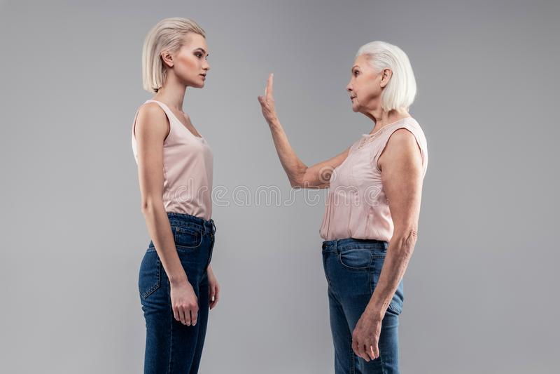 有突然移动停止姿态的理发陈列的老灰发的妇女 图库摄影