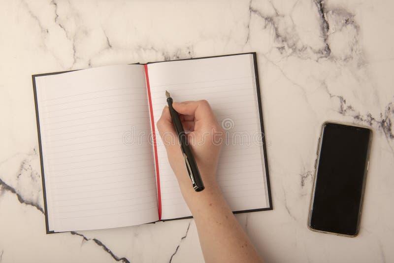 有笔的手在纸 库存图片