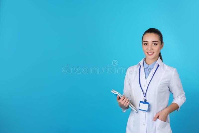 有笔记本的年轻医科学生在颜色背景 免版税库存图片