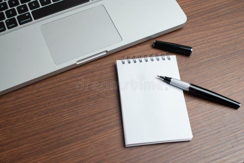 有笔记薄和笔的膝上型计算机 免版税库存照片