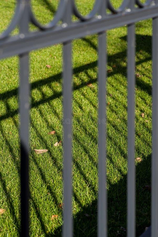有篱芭的阴影的绿色草坪 库存照片