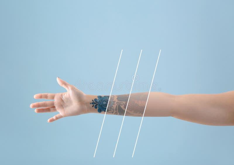 有纹身花刺的女性胳膊 免版税库存图片