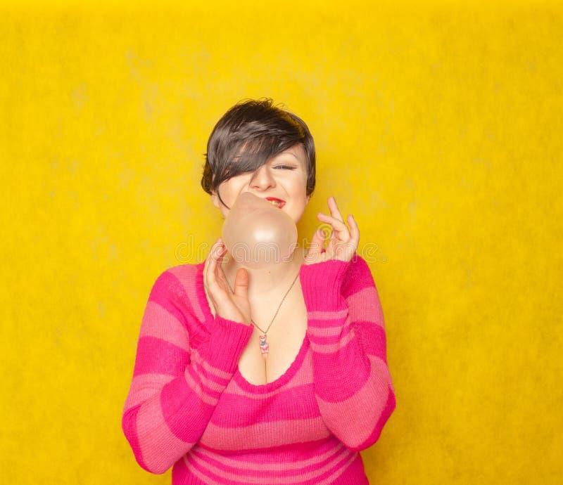 有短发的逗人喜爱的妇女嚼口香糖并且喘气在黄色背景的泡影 库存照片