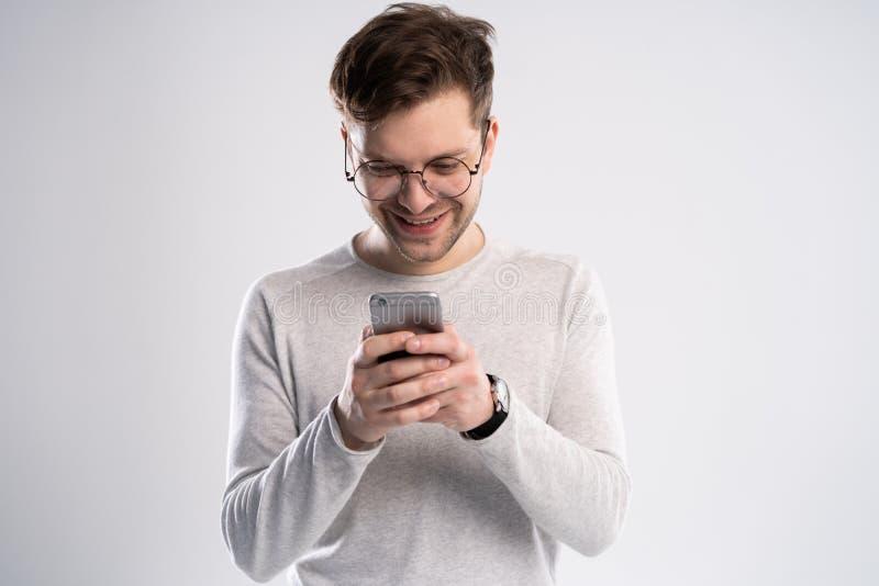 有短发聊天的或键入的短信的可爱的人使用手机被隔绝在白色背景 图库摄影