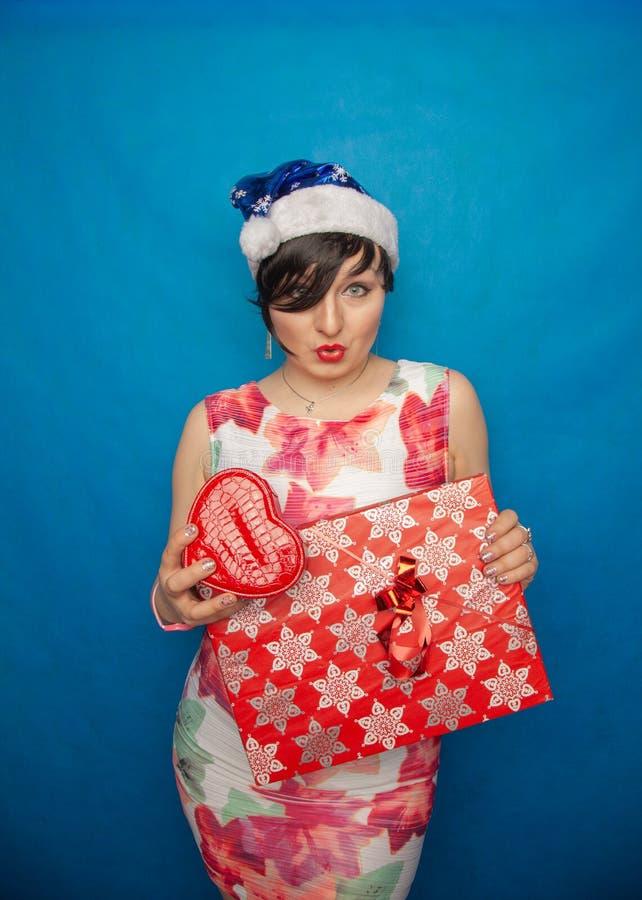 有短的黑色头发和圣诞老人帽子身分的肥满妇女在白色礼服有礼物盒的和很激发在蓝色演播室背景 库存照片