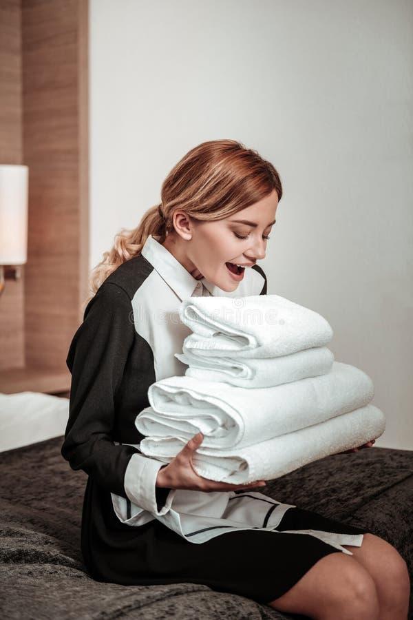 有看毛巾的白肤金发的卷发的美丽的旅馆佣人 免版税库存图片