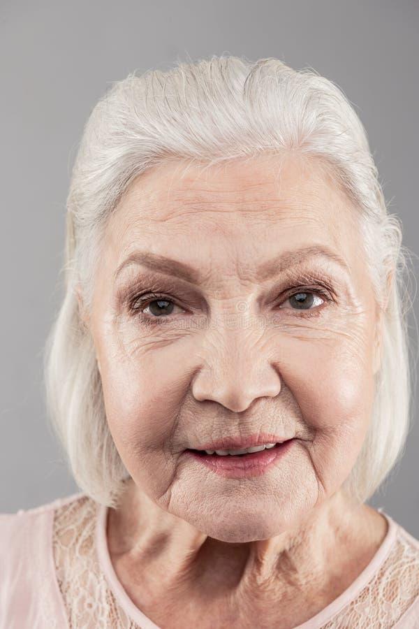 有看直接地入照相机的突然移动理发的老灰发的妇女 免版税库存图片