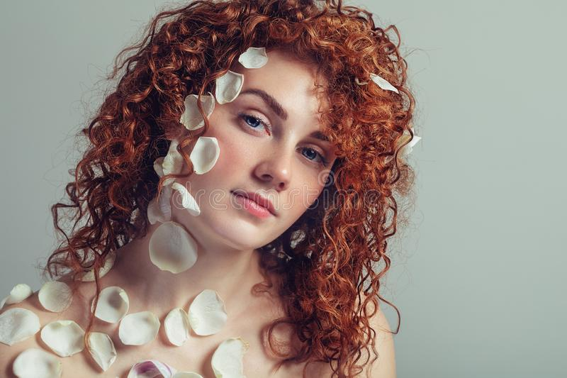 有玫瑰花瓣的美丽的年轻女人在她的面孔 P 库存照片