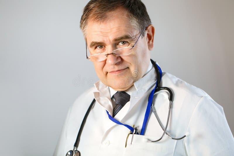 有玻璃和听诊器的医生调查他的眼睛 免版税库存图片