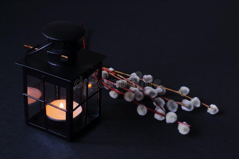 有燃烧的蜡蜡烛和杨柳枝杈的装饰黑金属灯笼在黑背景 概念—复活节,生活复兴  库存照片