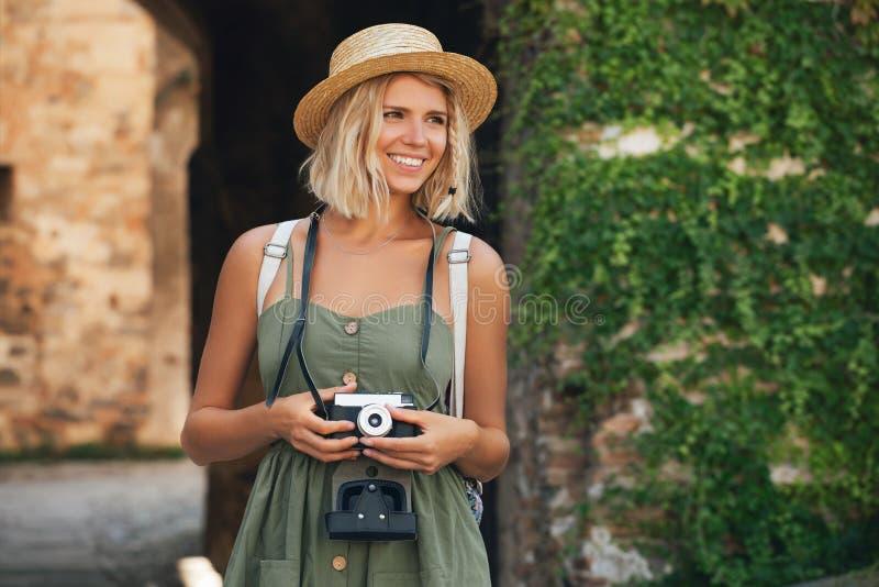 有照相机的愉快的旅游妇女 室外微笑的女孩的摄影师 图库摄影