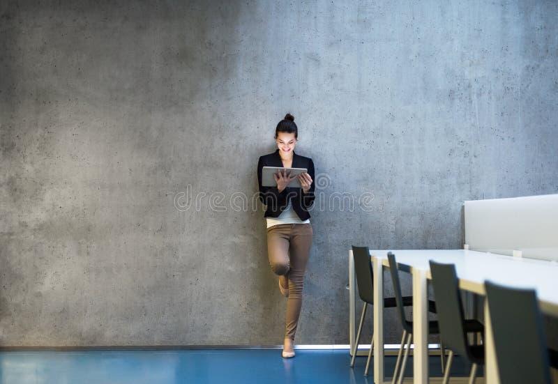 有片剂身分的年轻女商人对混凝土墙在办公室 免版税库存图片