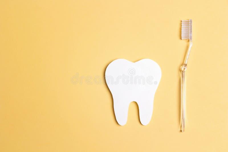 有牙刷的白皮书牙在黄色背景 牙齿健康概念 牙医天概念 库存图片