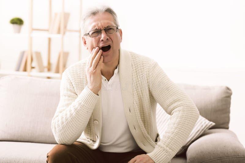 有牙痛和接触面颊的老人 图库摄影
