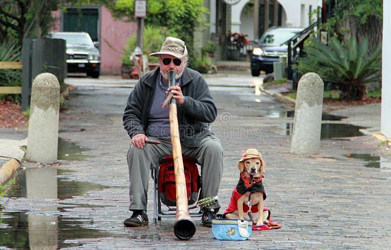 有狗的街道音乐家在圣奥斯丁在下雨天 免版税库存照片