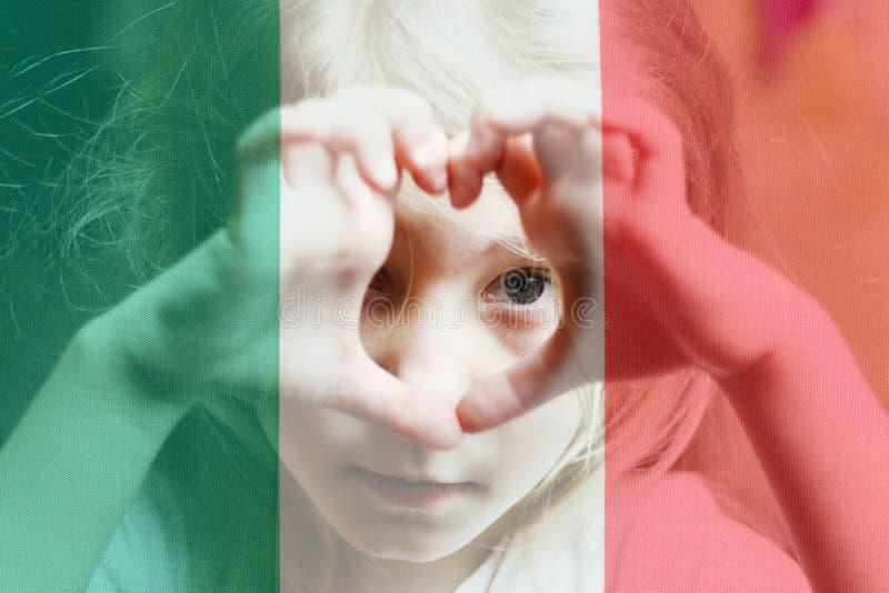 有白发的女孩做心脏和神色成它 以意大利旗子为背景 在网上学会意大利语 免版税图库摄影