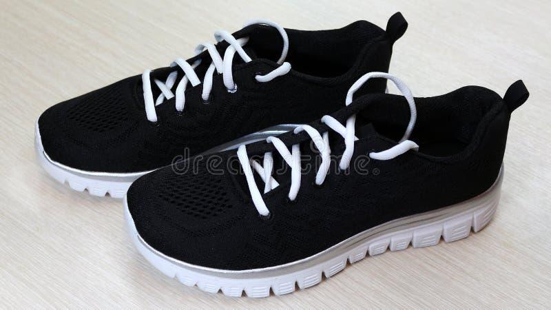 有白色单一和白色鞋带的黑男女皆宜的运动鞋在白色背景 库存图片