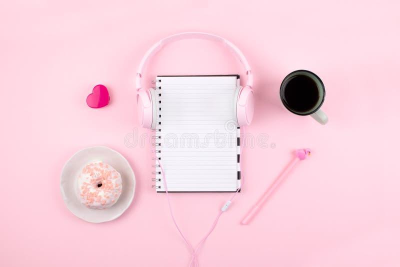 有白色空白的笔记薄、桃红色耳机、心脏、咖啡杯和多福饼的最小的工作场所在桃红色背景 顶视图 平的位置 免版税库存图片