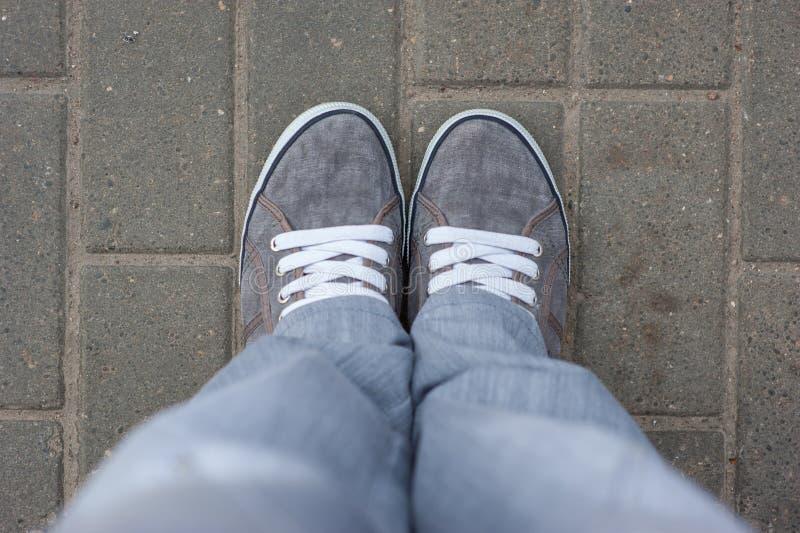 有白色鞋带的灰色运动鞋在瓦片,顶视图,走的鞋子站立在城市附近 灰色底下衣裳 库存图片