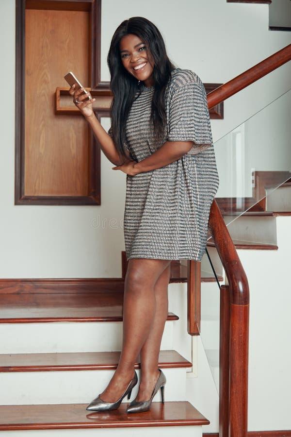 有电话的笑的时髦的黑人妇女在台阶 库存照片