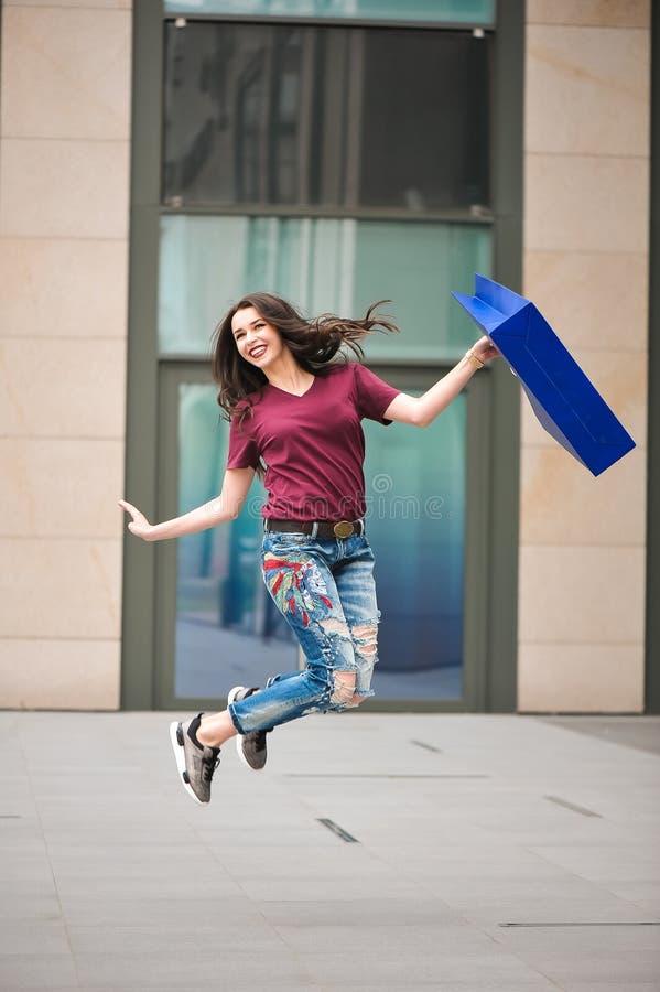 有袋子的可爱的女孩在她的手上 妇女和购物 美好的模型徒步审阅城市 库存图片