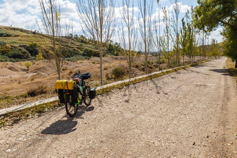 有袋子的旅客的自行车在一条空的石渣路站立 免版税库存照片