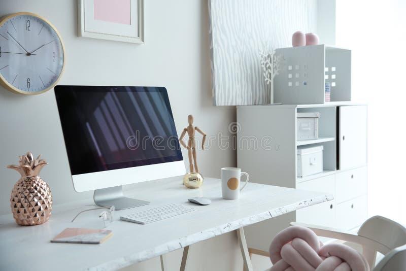 有计算机的当代工作场所在白色墙壁附近的桌上 免版税库存照片