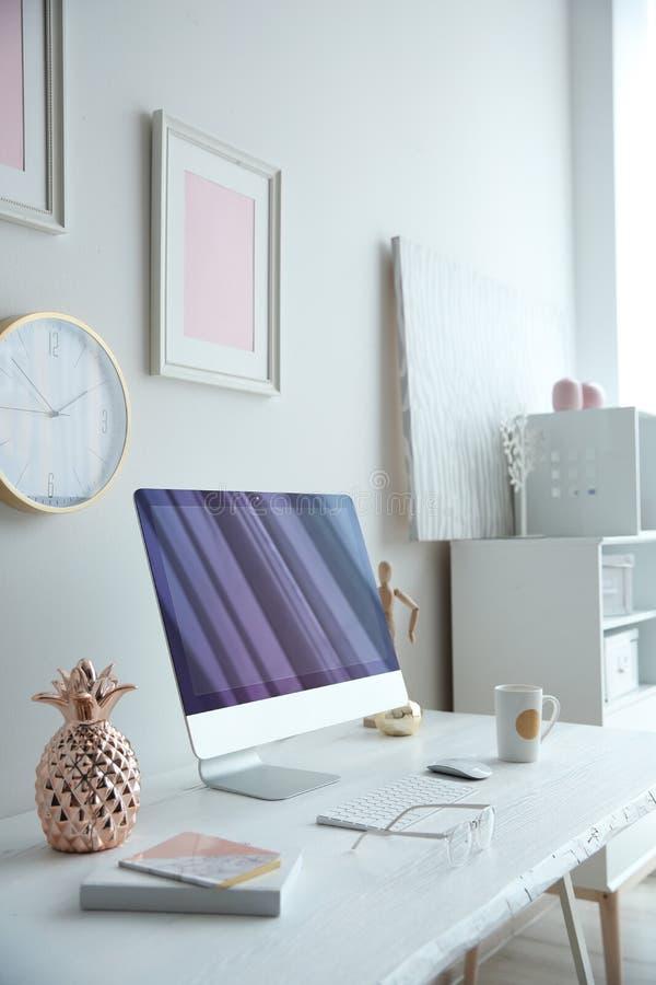 有计算机的当代工作场所在白色墙壁附近的桌上 库存图片