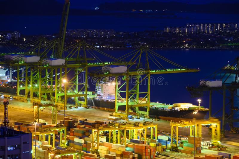有许多的港口起重机和货箱在黄昏期间 图库摄影