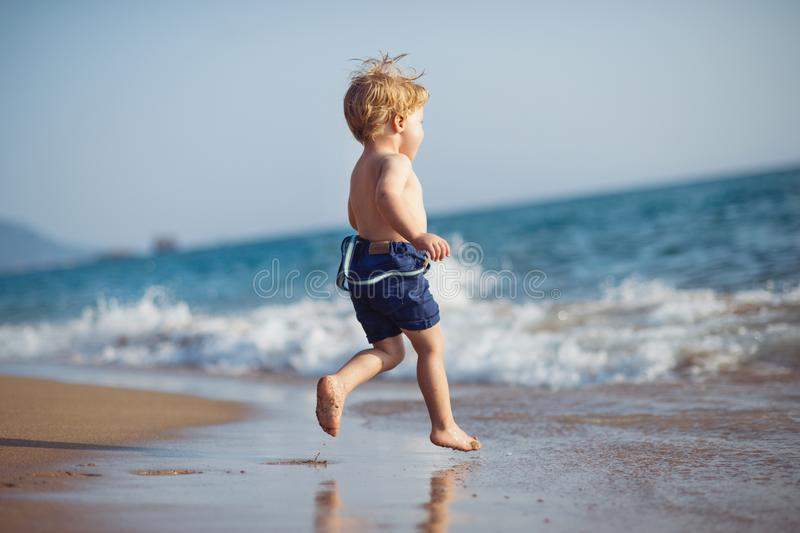 有跑在沙滩的短裤的一个小小孩男孩在度假夏天休假 库存图片
