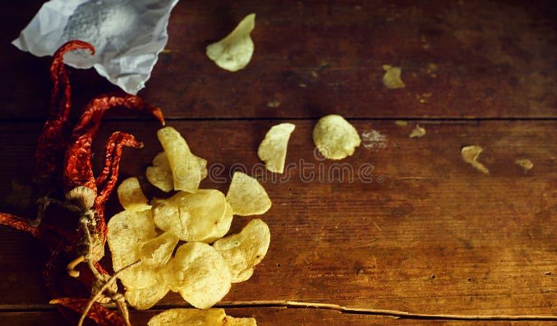 有辣子和盐的薯片在土气木桌上 库存图片