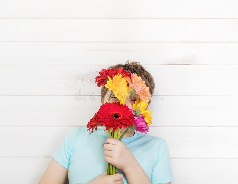 有花束大丁草花的逗人喜爱的男孩 免版税图库摄影