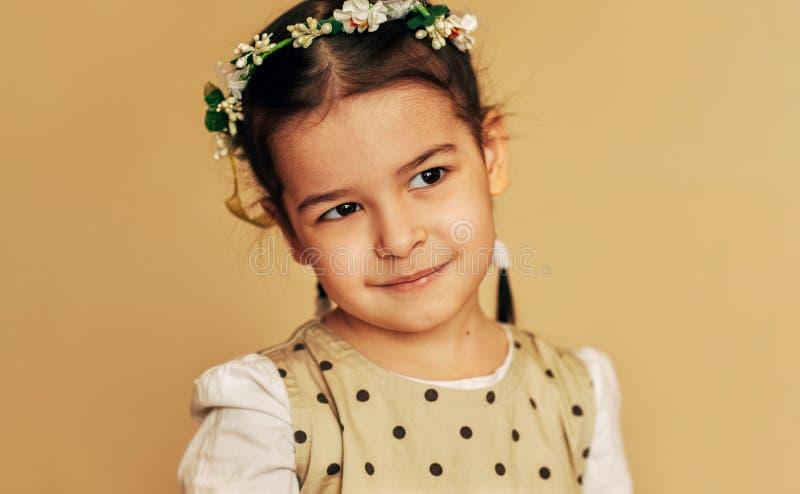 有花的美丽的女孩在她的头发,摆在为全家福在演播室 愉快可爱孩子女孩微笑 免版税库存图片