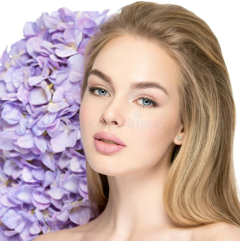 有花的美丽的年轻白肤金发的妇女临近面孔 库存照片