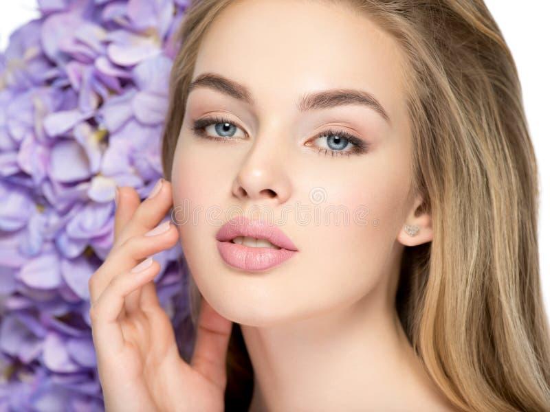 有花的美丽的年轻白肤金发的妇女临近面孔 免版税库存照片