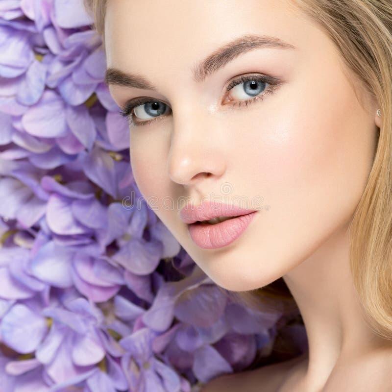 有花的美丽的年轻白肤金发的妇女临近面孔 库存图片