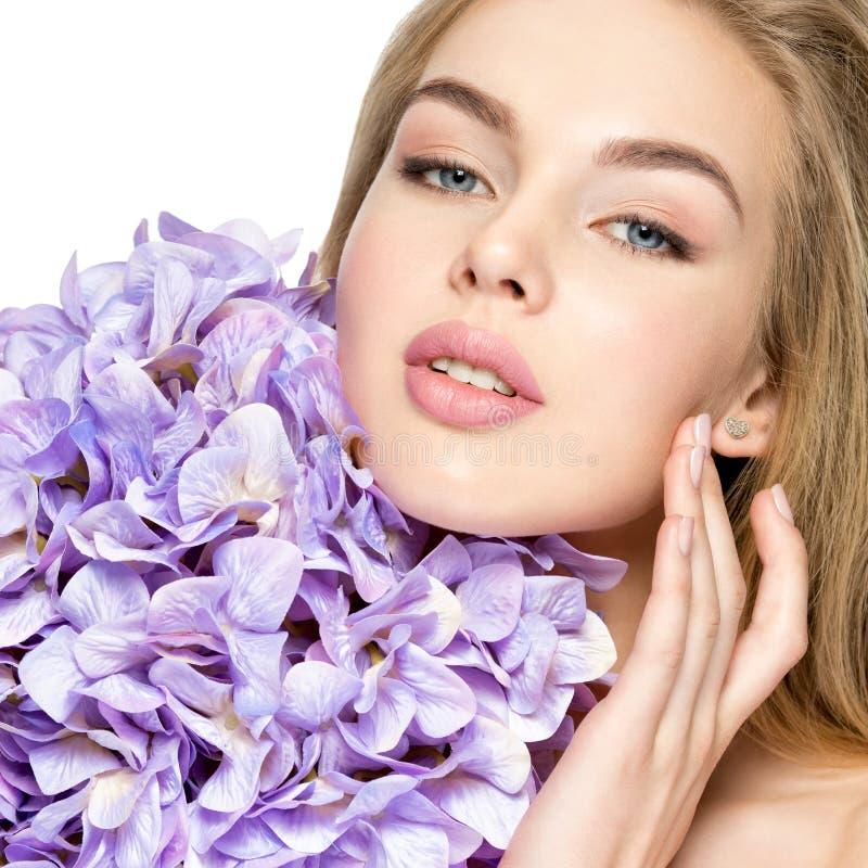 有花的美丽的年轻白肤金发的妇女临近面孔 免版税库存图片