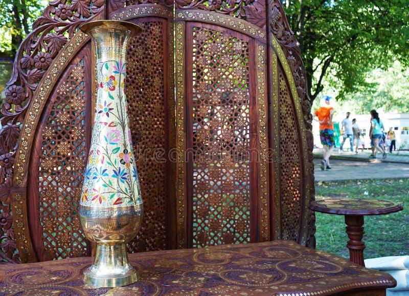 有花饰的被镀金的花瓶在桌上由桃花心木制成 免版税库存图片
