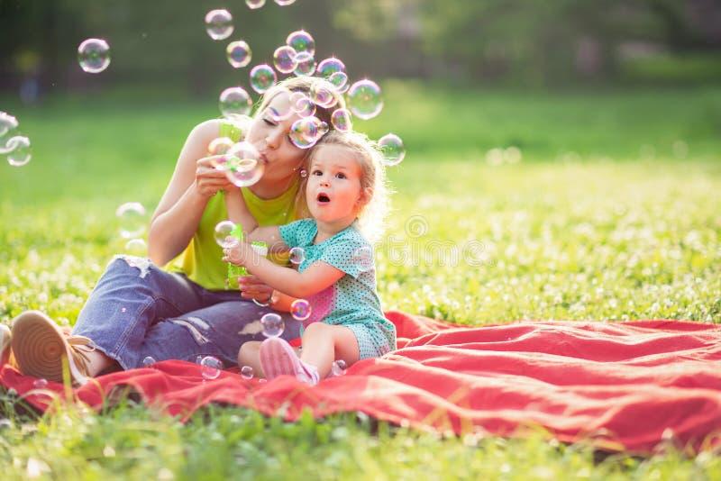 有获得他们的女儿的可爱的母亲乐趣 免版税库存图片
