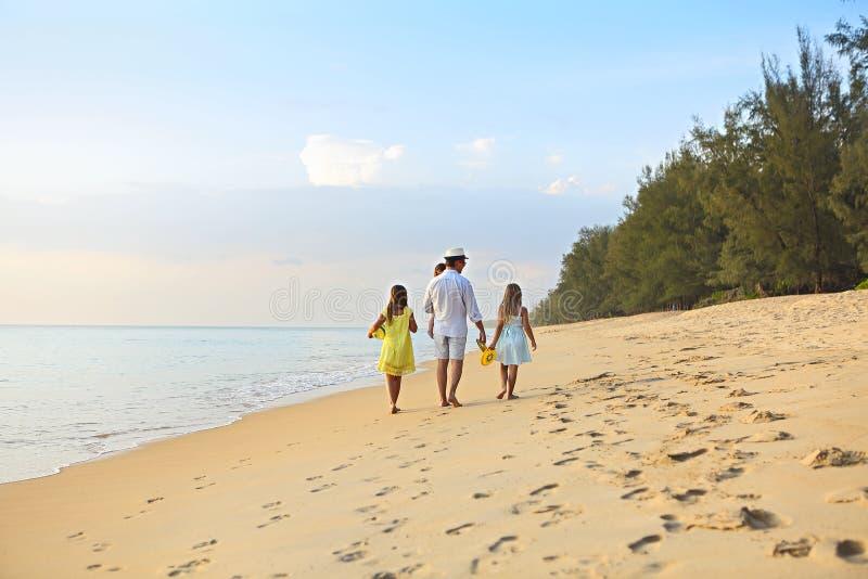 有获得在海滩的乐趣走在日落的孩子的愉快的父亲 免版税库存图片