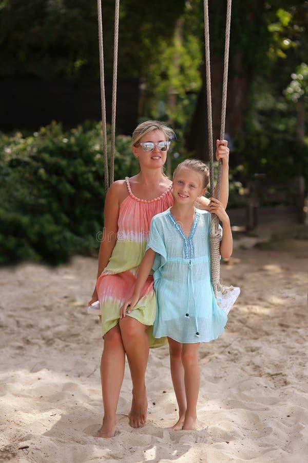 有获得的孩子的母亲摇摆在热带海滩的乐趣 库存图片