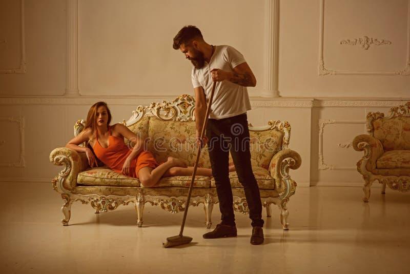 有胡子的人广泛地板,当妇女在沙发时放松,家事概念 执行家事人 我爱工作您怨恨 库存图片