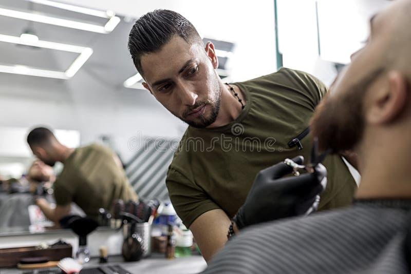 有胡子的时髦的人在镜子前面坐在理发店 理发师整理与剪刀的人的胡子 免版税库存图片
