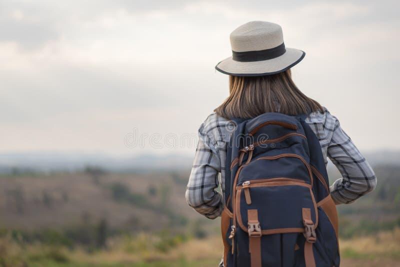 有背包的女性游人在乡下 免版税库存图片