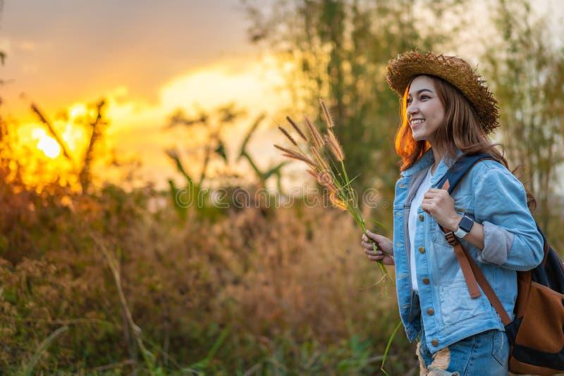 有背包的女性游人在有日落的乡下 库存照片