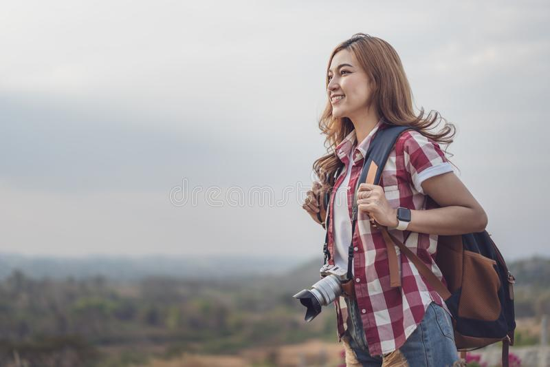 有背包的女性游人和照相机在乡下 库存照片