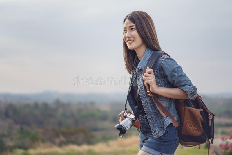 有背包的女性游人和照相机在乡下 免版税库存照片